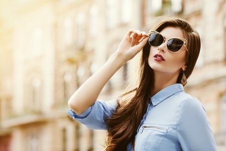 Outdoor-Porträt einer jungen schönen Frau zuversichtlich posiert auf der Straße. Modell trägt stilvolle Sonnenbrille. Mädchen auf der Suche nach oben. Weibliche Art und Weise. Sonniger Tag. Nahansicht. Stadt Lebensstil. Kopieren Sie Platz für Text