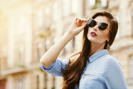 Outdoor portrait of a young beautiful confident woman posing on the street. Model wearing stylish sunglasses. Girl looking up. Female fashion. Sunny day. Close up. City lifestyle. Copy space for text Standard-Bild