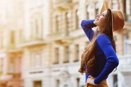Outdoor portrait of a young beautiful happy smiling woman posing on the street. Model wearing stylish hat and clothes. Girl looking up. Female fashion. Sunny day. Waist up. City lifestyle. Copy space