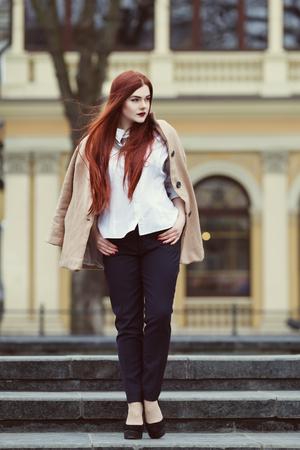 overweight students: Full body portrait of young beautiful lady wearing stylish classic clothes walking at street of the old city. Model looking aside. Female fashion concept. Toned Stock Photo