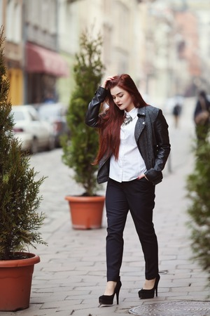 overweight students: Full body portrait of young beautiful lady wearing stylish classic clothes walking at street of the old city. Girl looking down. Plus size model. Female fashion concept. Toned