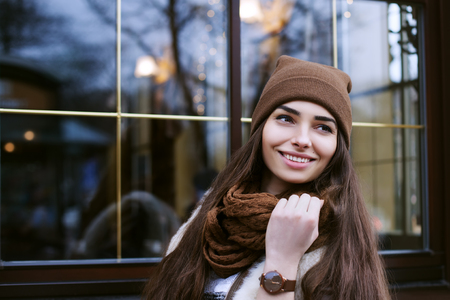 lady hand: Close up portrait of young beautiful smiling woman wearing stylish clothes standing on the street. Model looking aside. Female fashion concept. The window with light and reflections as a background.