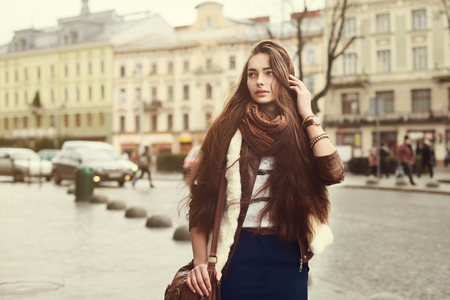 Straat portret van jonge mooie modieuze vrouw die stijlvolle kleding draagt die in de oude stad loopt. Model opzij kijken. Street mode concept. Detailopname. afgezwakt Stockfoto