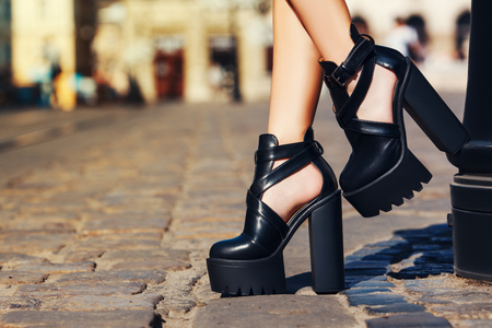 Elegant outfit. Closeup of stylish black leather summer shoes. Fashionable girl posing on street of the old city. Female fashion concept. Copy space. Toned.