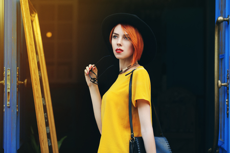 wistful: Outdoor portrait of young beautiful thoughtful lady walking on the street. Model wearing stylish summer clothes. Girl looking aside. Female fashion. City lifestyle. Sunny day. Waist up.