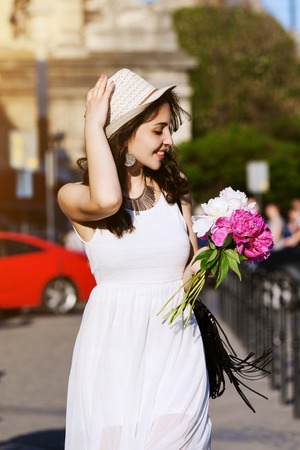 easy going: Outdoor portrait of young beautiful happy smiling lady walking on the street. Model wearing stylish white clothes and accessories. Girl looking down and aside. City lifestyle. Sunny day. Waist up. Stock Photo