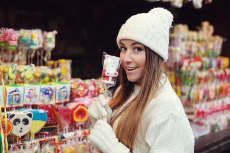 Street portrait of smiling beautiful young woman buying candy on the festive Christmas fair. Lady wearing classic stylish winter knitted clothes. Close up.