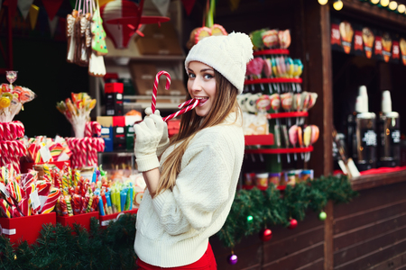 Street portrait of a smiling beautiful young woman biting Christmas candy cane and looking at camera. Lady wearing classic winter knitted clothes. Festive Christmas fair as background. Close up. Stock Photo
