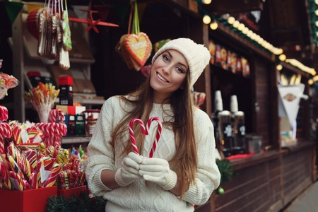 stilish: Street portrait of smiling beautiful young woman holding candy canes and looking at camera. Lady wearing classic stilish winter knitted clothes. Festive Christmas fair as backgruond. Close up. Toned.