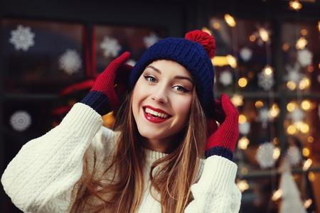 Retrato de la calle de la sonrisa de la mujer joven hermosa que lleva la ropa hecha punto invierno clásico elegante. Modelo que mira la cámara, luces festivas de la guirnalda. De cerca.