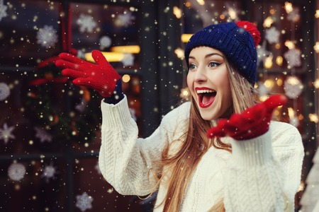 Street portrait of young beautiful woman acting thrilled, wearing stylish knitted clothes. Model expressing joy and excitement with hands and face. Festive garland lights. Magic snowfall effect. Close up. Toned.