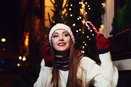 calle Retrato de la noche de la sonrisa hermosa mujer joven sentada en el café y hablando por teléfono móvil. Modelo mirando a un lado. Señora que lleva ropa de punto clásico de invierno. guirnalda luces festivas.