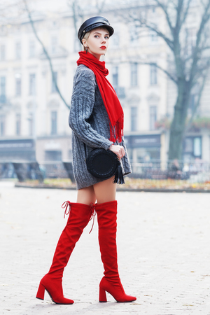 Outdoor full body portrait of young beautiful fashionable woman wearing trendy cap, red high, over knee boots, stylish clothes and accessories. Model walking in street. Elegant outfit. Female fashion