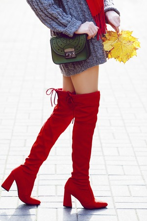 Fashionable woman wearing trendy red high, over the knee suede boots walking in street. Model holding small green textured bag and yellow autumn leafs. Elegant city outfit. Female fashion concept Stock Photo