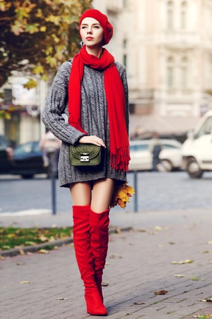 knee boots: Outdoor full body portrait of young beautiful fashionable woman wearing trendy red high, over knee boots, stylish clothes and accessories. Model posing in street. Elegant autumn outfit. Female fashion