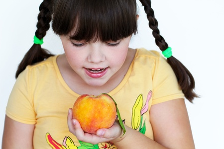Portrait of sweet young girl with peach photo