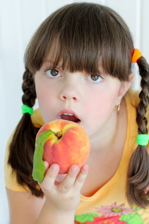 Young beautiful girl eating orange peach with green leaf