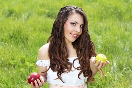 Smiling woman present apples in the garden Stock Photo - 10365996
