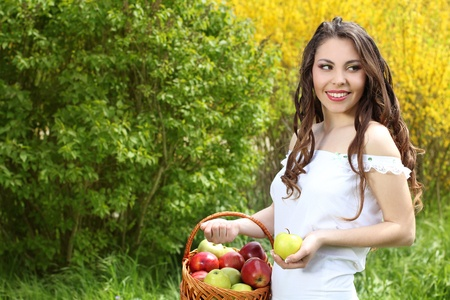 Happy young woman with apples at the basket. Spring Garden Stock Photo - 10365990