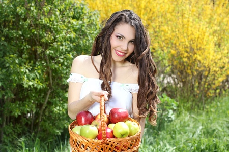 Girl in white dress presents basket of apples photo