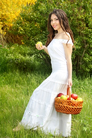 Girl in white dress is basket of apples photo