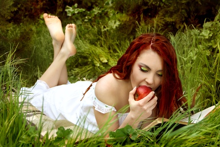 Young woman with red hair eat red apple on the nature photo