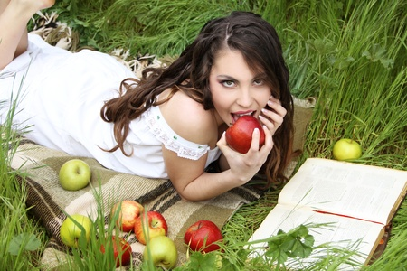 Beautiful girl eating apple in the green garden Stock Photo - 10366006