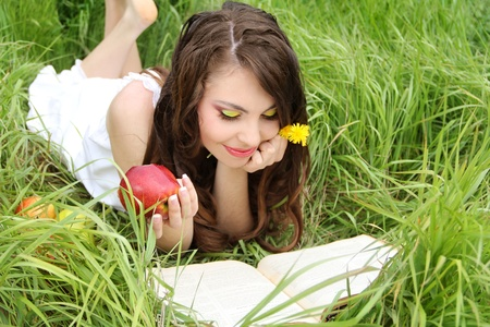 Charming woman with apples  on green grass and reads book. Springtime photo