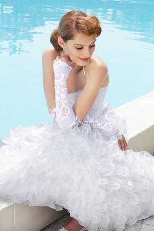 Beautiful bride posing near swimming pool in her wedding day photo