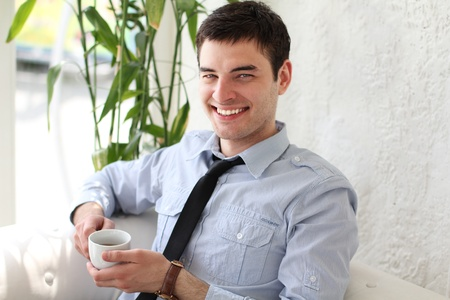 the well groomed: Young happy smiling man drinking coffee, outdoors Stock Photo