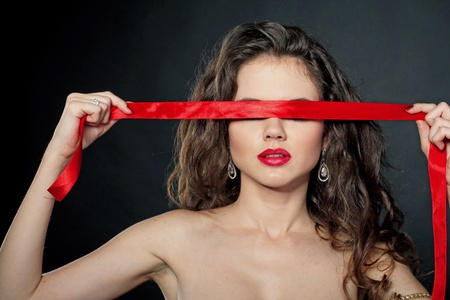 red ribbon covers face of Sexy woman, present gift