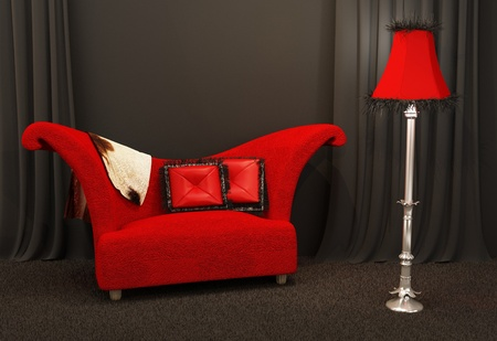 sofa furniture: Red fabric sofa. Textured and curved sofa with standing lapm in a dark interior
