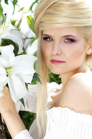 Portrait beauty blonde young woman with white lily, nature photo