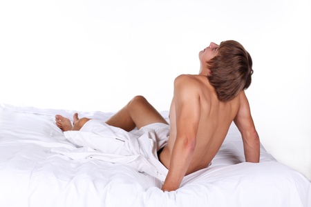 Young sexy man lying on white bed, thinking guy Stock Photo - 10511842