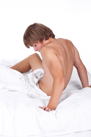 Young sexy man lying on white bed, thinking guy