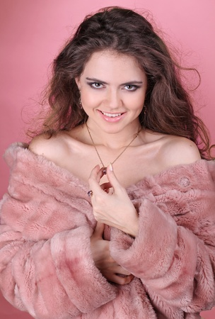 Beautiful smiling woman in winter fur coat over pink photo