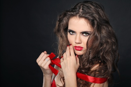 beauty girl on the black background, red lips and ribbon  photo