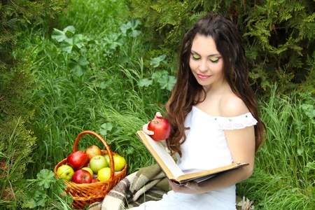 Beautiful girl reading the book with apples on Fairy tale  photo