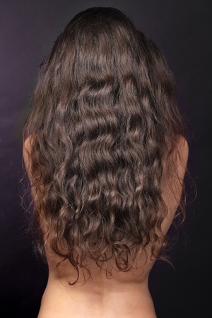 Woman with long curly hairs, back, brunette