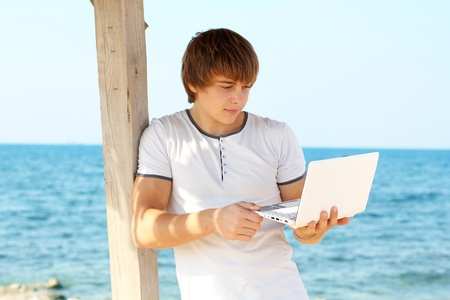one young man only: Young man using laptop at beach