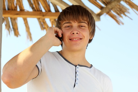 Young handsome man speaking on the beach using mobile phone photo
