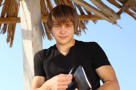 Handsome young man with writing pad, outdoors photo