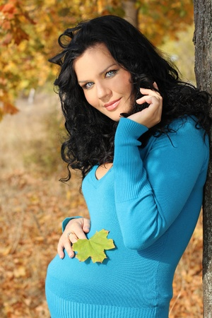feminity: Beautiful pregnant woman in blue jacket relaxing in the autumn park Stock Photo