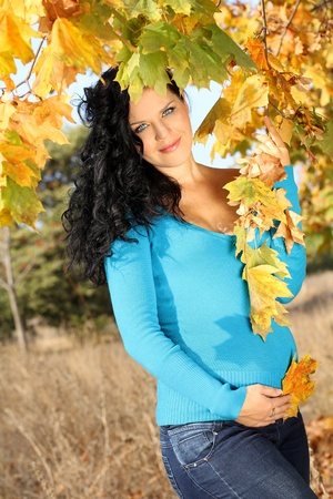 pregnant woman caressing her belly over autumn park, outdoors Stock Photo - 10854574
