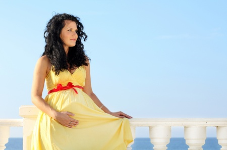 Pretty pregnant woman over sky in yellow dress Stock Photo - 10854548