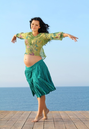 Flying happy pregnant woman on sea background photo