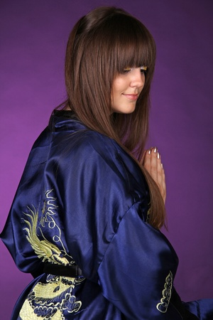 Back of woman in Oriental robe over dark purple  photo