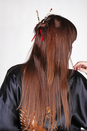 Japanese Geisha with red chopsticks in hairstyle, long hair photo