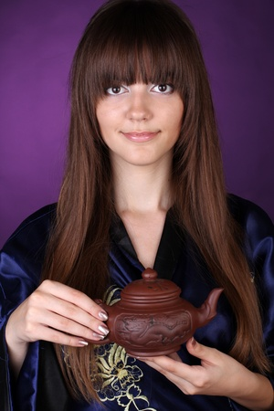 Tea ceremony beautiful woman with teapot on hands over purple photo