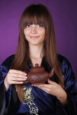 Tea ceremony happy woman with teapot on hands over purple photo